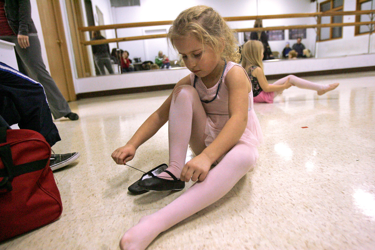 Monica Maschak - mmaschak@shawmedia.com Nataleen Fritz, 6, puts on her ballet shoes after taking off her tap shoes in the Ballet and Tap II class at the McHenry Municipal Building on Thursday, December 6, 2012.  Thursday was parent-watch night, where the parents of the dancers sat in on classes to see their child's progress.