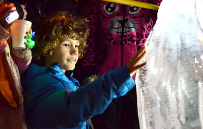 Monica Maschak - mmaschak@shawmedia.com Benjamin Kanner, 8, of Algonquin touches an ice sculpture at the Holiday Rock on The Fox in Algonquin on Saturday, December 1, 2012.  The event included the annual lighting of the tree, a visit from Santa, a candy-cane hunt, ice sculpting and more.