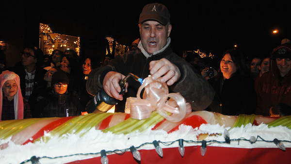 Chef Alain Roby of the All Chocolate Kitchen, puts the final touches on his 51 ft. candy cane, Saturday night night in downtown Geneva