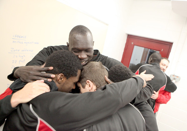 Mooseheart basketball player Makur Puoy (center), who is from South Sudan, hugs his teammates as they erupt in cheers upon hearing that they were cleared to play Tuesday and Wednesday.