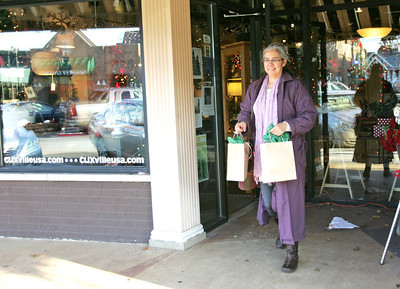 Monica Maschak - mmaschak@shawmedia.com Linda McDaniel, of Wauconda, walks out of the Clix store in downtown Crystal Lake on Thursday, December 13, 2012.  McDaniel came to Crystal Lake for the day to shop for gifts at the local stores.