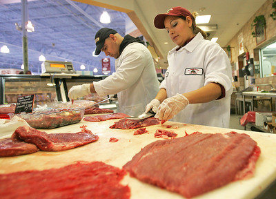 Monica Maschak - mmaschak@shawmedia.com Employees Manny Suarez (left) and Veronica Lopez prepare meat for ready-to-cook specialty foods at the Joe Caputo and Sons Fruit Market in Algonquin on Friday, December 14, 2012. The prices for beef, poultry and fresh fruit are expected to increase in 2013.
