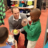 Chicago Bears kicker Robbie Gould talks with Mooseheart students Evan Tull, 5 (bottom left) and Yasin Adebayo, 6, (right) as they shop for gifts at Target in St. Charles. Over 80 Mosseheart students were each given $100 to spend courtesy of the Goulden Touch charity.