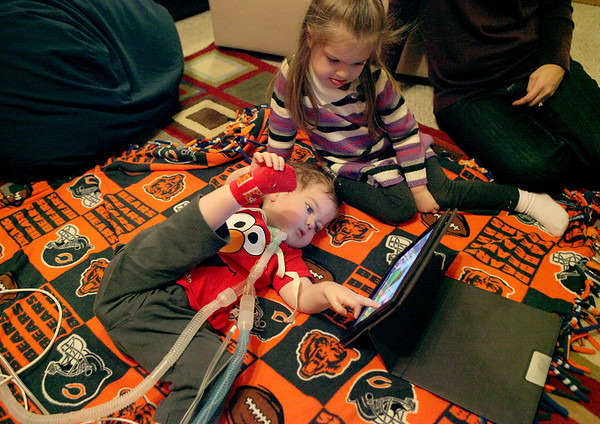 William Whiston, 17 months, plays on his iPad with his sister, Juliet, 3, in their Geneva home. William was born with myotubular myopothy, a rare genetic disorder that does not allow him to move his muscles with any force.