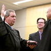 John Dalton is sworn in as the first openly gay judge in Kane County by Judge Keith Brown as Dalton's spouse, Rich Jacobs, looks on during a ceremony Thursday at the Kane County Branch Court in St. Charles.