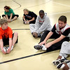 Mack Schweizer (center) leads the team in stretches before practice with the St. Charles East Fighting Saints Special Olympics basketball team.