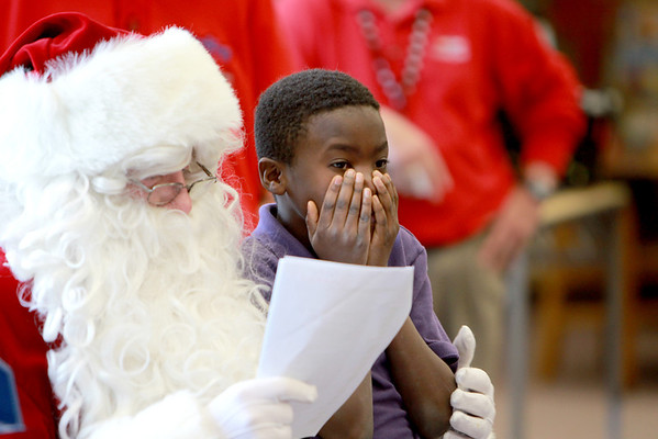 Mooseheart third-grader E.G. Barley visits with Santa at the school Friday morning. Bob Miller, principal  of Haines Middle School in St. Charles, has been portraying the jolly fellow for nine years.