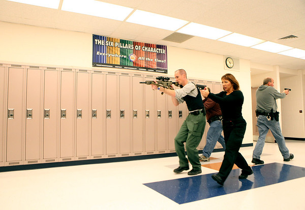 St. Charles Police officers use simunition, a non-lethal training ammunition, during a rapid deployment drill at the former Kaneland Middle School in Maple Park Thursday morning.
