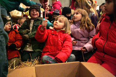 Monica Maschak - mmaschak@shawmedia.com Children from the audience gather around the manger to receive glow sticks to participate in the singing of a carol during the Marengo United Methodist Church annual Live Nativity service at Cody's Farm on Christmas Eve.