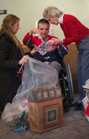 Danny S. and his mother, Caryl Schwartz, on right, opens gifts with 20-year-old Jill Langlas, on left, from Wheaton Warrenville South High School at Marklund at Mill Creek in Geneva Monday, Dec. 24.
