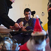 Ashish P. opens gifts on Christmas Eve with volunteers from Wheaton Warrenville South High School at Marklund at Mill Creek in Geneva Monday, Dec. 24.