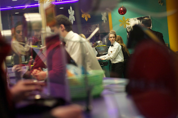 Jackie Selig, 16, works at the ticket booth Christmas Day at Cinema 18 in Charlestown Mall.