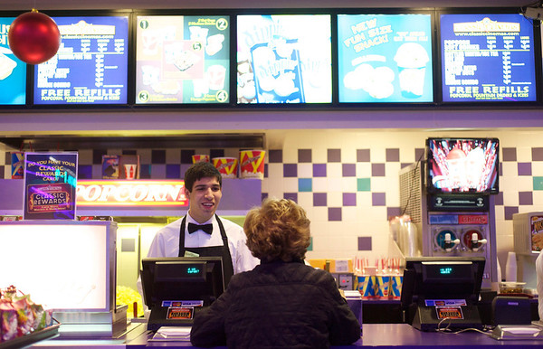 7-year-old Eddy Rubio works the concession stands at Cinema 18 in Charlestown Mall on Christmas Day.