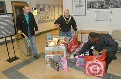 City employee Noel Basquin (from left) lends a hand on Tuesday, Dec. 4, 2012, as Rudy Dubis and Roy Bailey, both of Batavia, who are members of the Batavia Access Committee, get ready to carry out toys collected at Batavia City Hall, that were donated at the previous night's city council meeting. The committee is in desperate need of toys, especially for older kids, to donate to Batavia families in need. Staff photo by Bill Ackerman