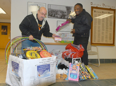 On Tuesday, Dec. 4, 2012, Rudy Dubis (left) and Roy Bailey, both of Batavia, who are members of the Batavia Access Committee, collect toys at Batavia City Hall, that were donated at the previous night's city council meeting. The committee is in desperate need of toys, especially for older kids, to donate to Batavia families in need. Staff photo by Bill Ackerman