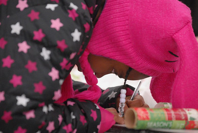 Samahri Davenport, 9, of Bolingbrook signs a card for one of her Christmas gift purchases during the annual Shop with a Cop event at Meijer, 755 E. Boughton Rd. on Tuesday, Dec. 18, 2012. Matthew Piechalak — mpiechalak@shawmedia.com
