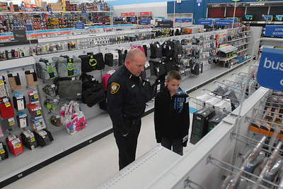 Bolingbrook Police Chief Kevin McCarthy helps Cody Luttrell, 10, of Bolingbrook, shop for Christmas gifts during the annual Shop with a Cop event at Meijer, 755 E. Boughton Rd. on Tuesday, Dec. 18, 2012. Matthew Piechalak — mpiechalak@shawmedia.com