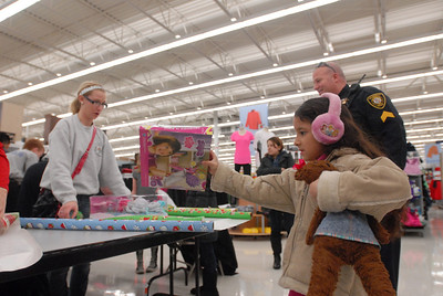 Naomy Ramirez, 7, of Bolingbrook places a gift on the counter to be wrapped during the annual Shop with a Cop event at Meijer, 755 E. Boughton Rd. on Tuesday, Dec. 18, 2012. Matthew Piechalak — mpiechalak@shawmedia.com
