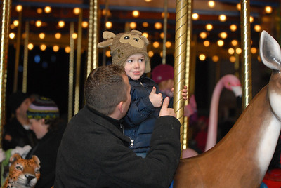 """Brent Chamberlain and his son, Griffin, 3, of Hampshire, give each other """"thumbs up"""" while riding on the Merry-Go-Round during the Holiday Magic event at Brookfield Zoo on Saturday, Dec. 8, 2012. Staff photo by Matthew Piechalak"""