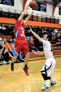 Sarah Nader - snader@shawmedia.com Marian Central's Matt Yuk (left) shoots over Crystal Lake Central's Brad Knoeppel during the second quarter of Tuesday's game in Crystal Lake on December 11, 2012.
