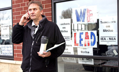 H. Rick Bamman - hbamman@shawmedia.com Striking Jacobs High School teacher Robert Frazier takes a call outside union strike headquarters and warming center in West Dundee. District 300 and its teachers union vehemently disagreed on whether lower class sizes or higher compensation derailed a last-ditch bargaining session Monday that led to the first district labor strike since 1972.