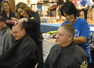 Broadview police officers Tom Ackerman (left) and Ken Klamer get extremely close hair cuts from Hilga Delacruz (left) and Jovi Evans as part of a Komarek School fundraiser on Wednesday, Dec. 19, 2012, for Daniele Santucci, 6, who is being treated for liver cancer. Bill Ackerman — backerman@shawmedia.com