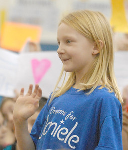 Komarek School first-grader Katie Fedorski, 6, waves to her neighbor Daniele Santucci at a school pep rally and fundraiser on Wednesday, Dec. 19, 2012, being held for Daniele, 6, who is being treated for liver cancer. Bill Ackerman — backerman@shawmedia.com
