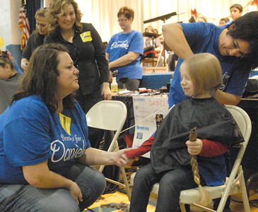 Dana Santucci holds the hand of Madeline Ehrenberg, 4, of Darien, as she has the other braid cut off by Jovi Evans, to be donated to Locks of Love. The Komarek School community holds a pep rally and fundraiser on Wednesday, Dec. 19, 2012, for Dana's daughter, Daniele, 6, who is being treated for liver cancer. Madeline's mom and dad are North Riverside police officers. Bill Ackerman — backerman@shawmedia.com