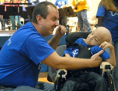 Tony Santucci adjusts his daughter, Daniele, 6, in her wheelchair after they make an entrance in the packed Komarek School gym. The Komarek community holds a pep rally and fundraiser on Wednesday, Dec. 19, 2012, for classmate, Daniele, who is being treated for liver cancer. Bill Ackerman — backerman@shawmedia.com