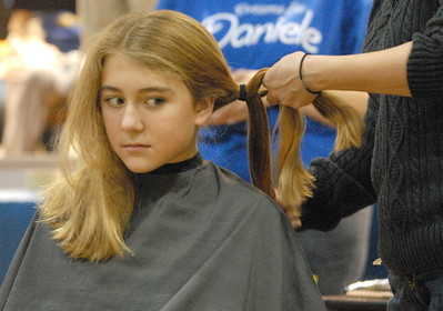 Fifth grader Moira Ford, 11, of North Riverside, watches out of the corner of her eye as her hair is braided in preparation for it being cut and donated to Locks of Love. The Komarek School community holds a pep rally and fundraiser on Wednesday, Dec. 19, 2012, for classmate, Daniele Santucci, 6, who is being treated for liver cancer. Bill Ackerman — backerman@shawmedia.com