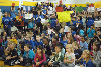 The Komarek School community packs the school gym, many holding signs of support, as they hold a pep rally and fundraiser on Wednesday, Dec. 19, 2012, for their friend and classmate, Daniele Santucci, 6, who is being treated for liver cancer. Bill Ackerman — backerman@shawmedia.com