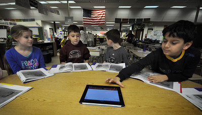 A group of El Sierra fourth graders use an iPad to record a story during class Wednesday morning. Staff photo John Cox