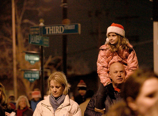 Olivia Blonsky, 10, sits high on her dad, Adam's, shoulders as her mom, Lynn, looks on during the annual Geneva Christmas Walk Friday night.(Sandy Bressner photo)