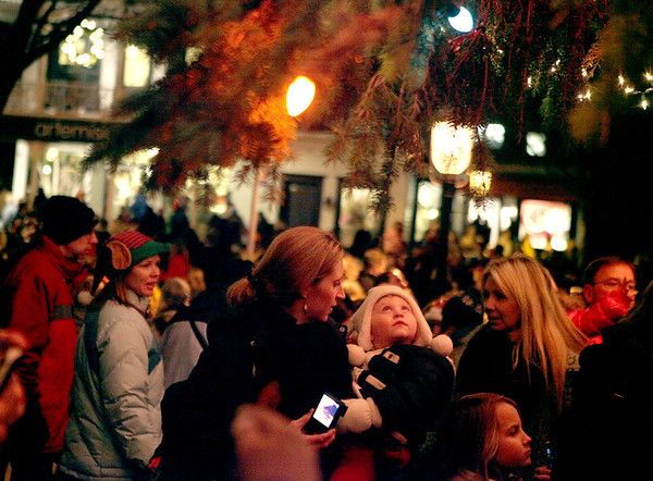 Megan Hotchkiss and her daughter, Ella, 2, look up at the lights after the City of Geneva's Christmas tree was lit during the annual Geneva Christmas Walk Friday night .(Sandy Bressner photo)