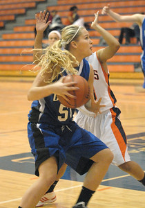 Geneva's Janie McCloughan drives to the basket, drawing a foul from Naperville North's Zoe Swift in Naperville on Saturday, Dec. 15, 2012, winning 43-32.  Bill Ackerman — backerman@shawmedia.com