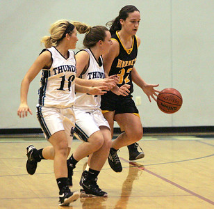 Monica Maschak - mmaschak@shawmedia.com Harvard's Abby Linhart moves down the court followed by two opponents during a game at Woodstock North on Monday, December 3, 2012. Harvard lost to Woodstock North 43-24.