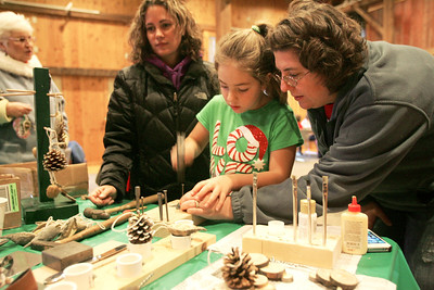 Monica Maschak - mmaschak@shawmedia.com Katie Diakow (right) helps her daughter Shelby to punch holes into her tin ornament at the McHenry County Conservation District's Historical Holidays on Saturday, December 15, 2012. Attendees were able to make crafts and ornaments from the 1850s at the 1902 Wiedrich Barn.