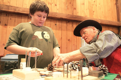 Monica Maschak - mmaschak@shawmedia.com Bill Scarlett (right), a volunteer, helps eight-year-old Quin Barry make a wooden snowman ornament at McHenry County Conservation District's Historical Holidays at Glacial Park on Saturday, December 15, 2012.