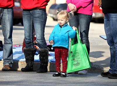 Josh Peckler - Jpeckler@shawmedia.com Samantha Long, 2 of Lake in the Hills holds a bag as she waits for candy to be thrown out during the Merry Cary Holiday Parade in downtown Cary Sunday, December 2, 2012.