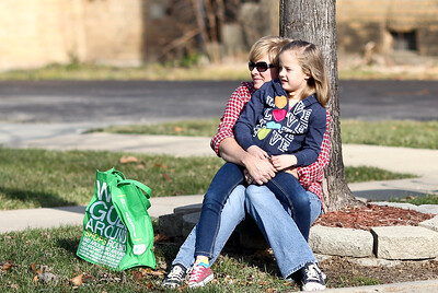Josh Peckler - Jpeckler@shawmedia.com Lilly Elliott, 7 of Cary sits on the lap of her mother Kimberly as they wait for the Merry Cary Holiday Parade in downtown Cary to start on Sunday, December 2, 2012.