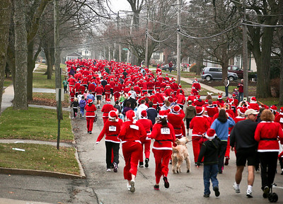 Josh Peckler - Jpeckler@shawmedia.com Runners dressed as Santa run down Williams Street in downtown Crystal Lake as the compete in the Santa Run-Walk for Kids in downtown Crystal Lake Sunday, December 2, 2012. Hundreds of runners dressed in Santa suits and reindeer antlers to raise money for children in Mchenry County.
