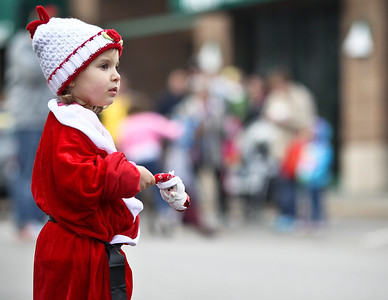 Josh Peckler - Jpeckler@shawmedia.com Angelica Hill, 3 watches as runner compete in the Santa Run-Walk 5K for Kids in downtown Crystal Lake Sunday, December 2, 2012. Hundreds of runners dressed in Santa suits and reindeer antlers to raise money for children in Mchenry County.