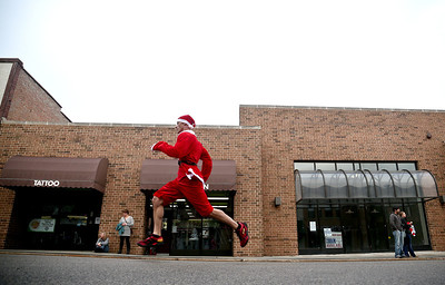 Josh Peckler - Jpeckler@shawmedia.com A runner dressed as Santa competes in the Santa Run-Walk 5K for Kids in downtown Crystal Lake Sunday, December 2, 2012. Hundreds of runners dressed in Santa suits and reindeer antlers to raise money for children in Mchenry County.