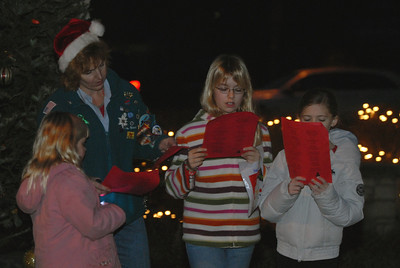 Unit 724 Girl Scouts Olivia Tolly, 6, from right, Charlotte Tolly, 9 and Megan Bechtlofft, 9, sing Christmas carols during Hometown Holidays in Lemont on Saturday, Dec. 1, 2012. Also pictured, Girl Scout Event Chairperson Betty Slad. Staff photo by Matthew Piechalak