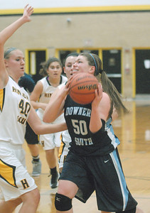 Downers Grove South's Kirsten Zemke draws a foul from Hinsdale South's Kerry Just as she drives to the basket in Darien on Tuesday, Dec. 11, 2012. Staff photo by Bill Ackerman