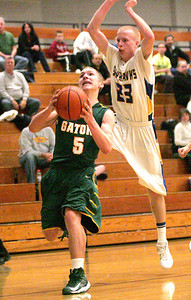Monica Maschak - mmaschak@shawmedia.com Crystal Lake South's Alex Bartusch (5) leaps to the hoop as Johnsburg's Kevin Dombrowski jumps to block from behind in a close game on Wednesday, December 5, 2012.  Johnsburg won 45-42.