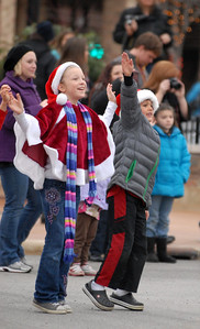 Keya Porch, 9, of Lisle and Alexander Barger, 8, of Naperville enthusiastically wave as Santa Claus rides past during the annual Lights of Lisle Festival along Main Street on Saturday, Dec. 1, 2012. Staff photo by Matthew Piechalak