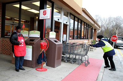 Tracy Mayberry rings her bell as a Jewel-Osco employee brings carts into the store. Staff photo by Sarah Minor