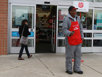 Louis Lumpkin rings his bell at the Walgreens in Lisle as a customer walks by on Friday, Dec. 7. Staff photo by Sarah Minor
