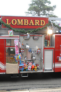 Donated toys line the side of a Lombard fire truck during the annual Lombard Fire Department Toy Parade along Main Street on Saturday, Dec. 8, 2012. Staff photo by Matthew Piechalak